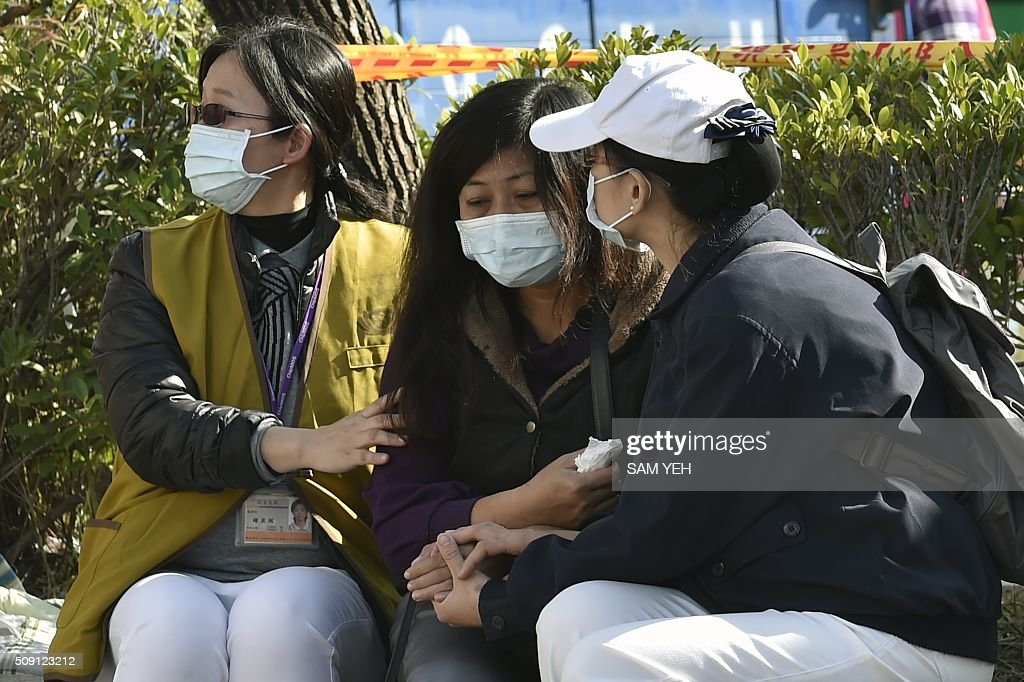 A relative (C) of victims trapped inside the Wei-Kuan complex during the 6.4 earthquake is cared for by volunteers in Tainan, southern Taiwan, on February 9, 2016. Rescuers deployed heavy machinery in a renewed effort to locate more than 100 people trapped in the rubble of a Taiwan apartment complex felled by an earthquake as the 72-hour 'golden window' for finding survivors passed. AFP PHOTO / Sam Yeh / AFP / SAM YEH