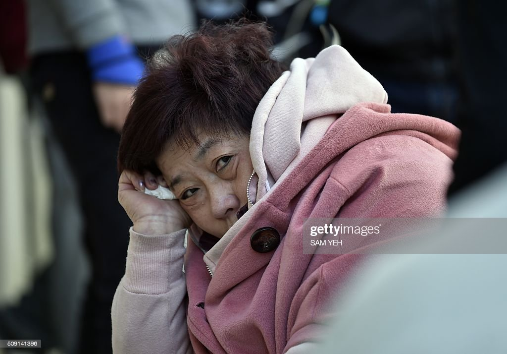 A relative of victims trapped inside the Wei-Kuan complex which collapsed during the 6.4 magnitude earthquake listens during a city government meeting in Tainan, southern Taiwan, on February 9, 2016. Rescuers deployed heavy machinery on February 9 in a renewed effort to locate more than 100 people trapped in the rubble of a Taiwan apartment complex felled by an earthquake as the 72-hour 'golden window' for finding survivors passed. AFP PHOTO / Sam Yeh / AFP / SAM YEH