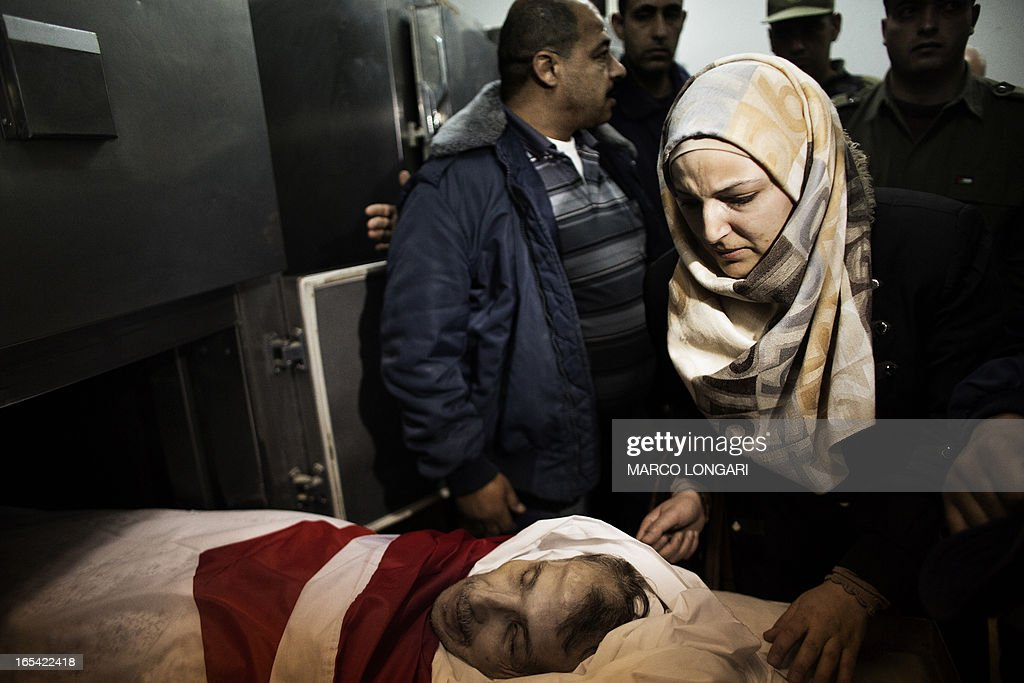 A relative stands next to the body of Maisara Abu Hamdiyeh, a Palestinian prisoner who died of cancer while in detention, at the Al-Ahli hospital in the West Bank city of Hebron ahead of his funeral on April 4, 2013. The Palestinian leadership has accused Israel of medical negligence, despite moves by the prison service to secure his early release on compassionate grounds, with news of his death sparking angry clashes with the army, notably in Hebron.