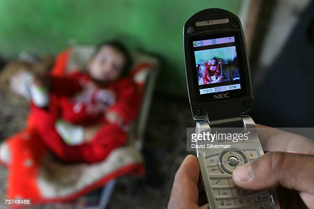 A relative uses a mobile phone to photograph Muhammad Abu Kef a 2 1/2 year old Bedouin Arab boy in his rocker in his family's home March 29 2007 in...