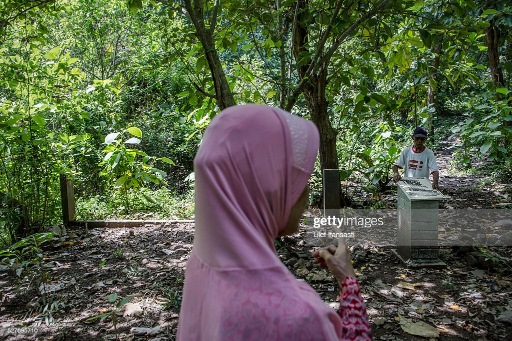 A relative visits the site that is believed to be the burial ground for victims of Indonesia's anti-communist massacre, inside the teak forest in Plumbon village on May 03, 2016 in Semarang, Central Java, Indonesia. Survivors of Indonesia's anti-communist massacres called for investigations into the country's purges, in which possibly half a million to one million people died beginning October 1965, during the crackdown by the Indonesian government and military after an attempted coup by suspected communists.