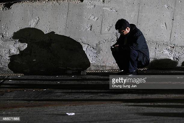 A relative waits for missing passengers of a sunken ferry at Jindo port on April 16 2014 in Jindogun South Korea Four people are confirmed dead and...