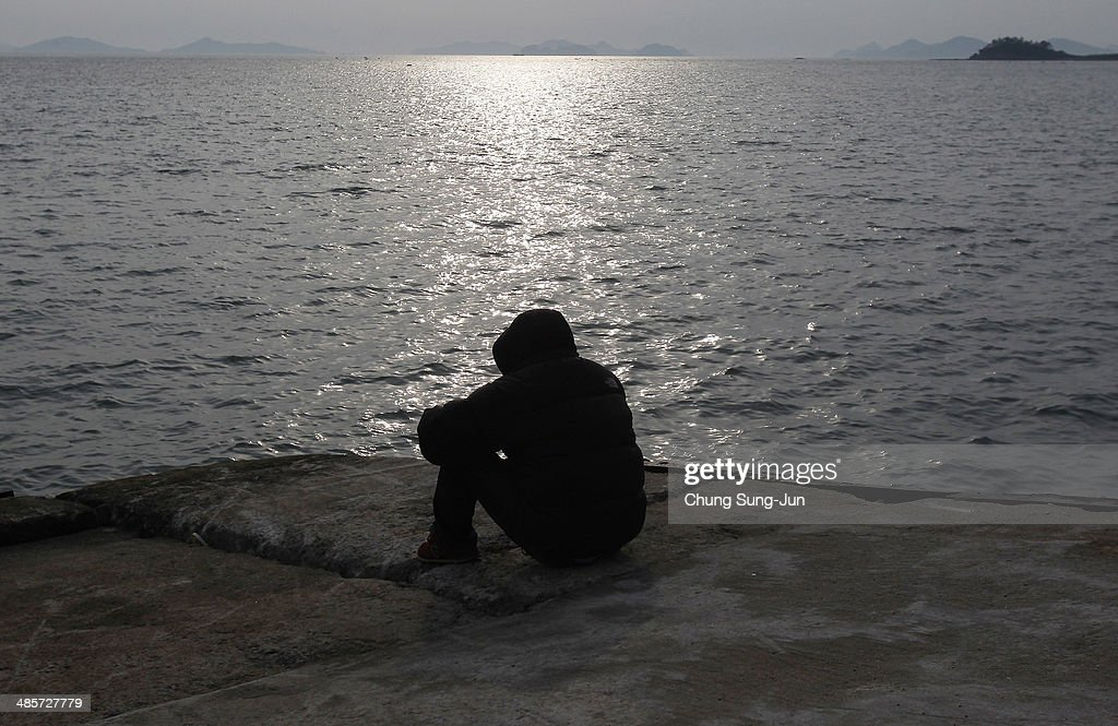 A relative waits for missing passengers of a sunken ferry at Jindo port on April 20, 2014 in Jindo-gun, South Korea. At least fifty eight people are reported dead, with 244 still missing. The ferry identified as the Sewol was carrying about 470 passengers, including the students and teachers, traveling to Jeju Island.