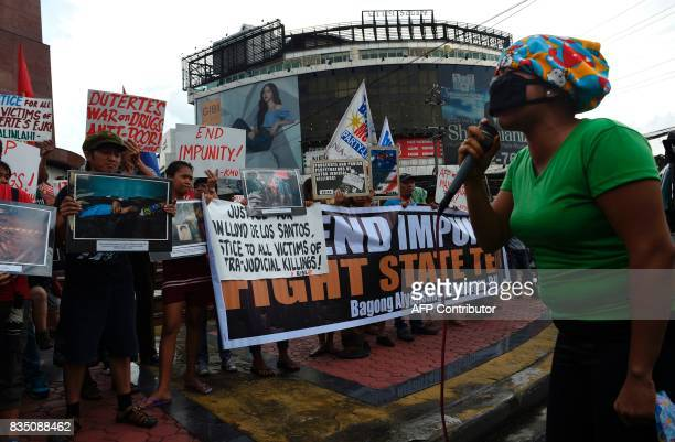 A relative wearing a mask to hide her face speaks during a protest against extra judicial killings as other relatives hold portrait of the victims...