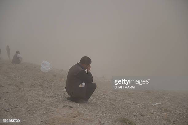 A relative weeps as Afghan men dig the graves for victims of a twin suicide attack in Kabul on July 24 2016 Kabul was plunged into mourning on July...