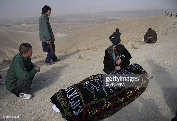 TOPSHOT A relative weeps next to the coffin of one of the 27 victims killed in a bloody mosque bombing in Kabul on November 23 2016 An international...