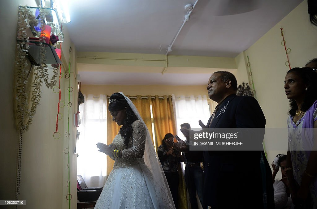 Relatives along with bride Emilia D'Silva (L) pray before an altar before leaving home for a marriage ceremony at the Mount Mary church in Mumbai on December 12, 2012. Couples may be rushing down the aisle on 12/12/12 today in hope of an auspicious union, but Brandon Pereira and Emilia D'Silva can claim an even rarer set of special dates. Brandon Pereira and Emilia D'Silva who have known each other for over 10 years now celebrated their engagement on 10/10/10, had a registered legal marriage on 11/11/11 and finally had their big white wedding in Mumbai on 12/12/12.