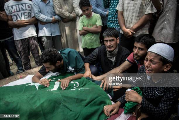 Relatives amp friends cry near the body of local rebel Adil Ahmed during his funeral procession Saturday June 17 on the outskirts of Srinagar...