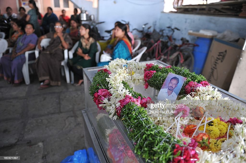 Relatives and family members sit beside Sukka Venkateshwarlu, lying in a coffin after dying in a bomb blast, in Hyderabad on February 22, 2013. The twin blasts killed 14 people and wounded dozens more in a busy neighbourhood in the southern Indian city. AFP PHOTO / NOAH SEELAM