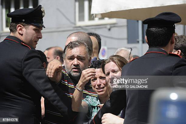 Relatives and friends are blocked by policemen while some of the 109 people linked to a drug traffic are escorted to jail in Naples on May 19 2009...