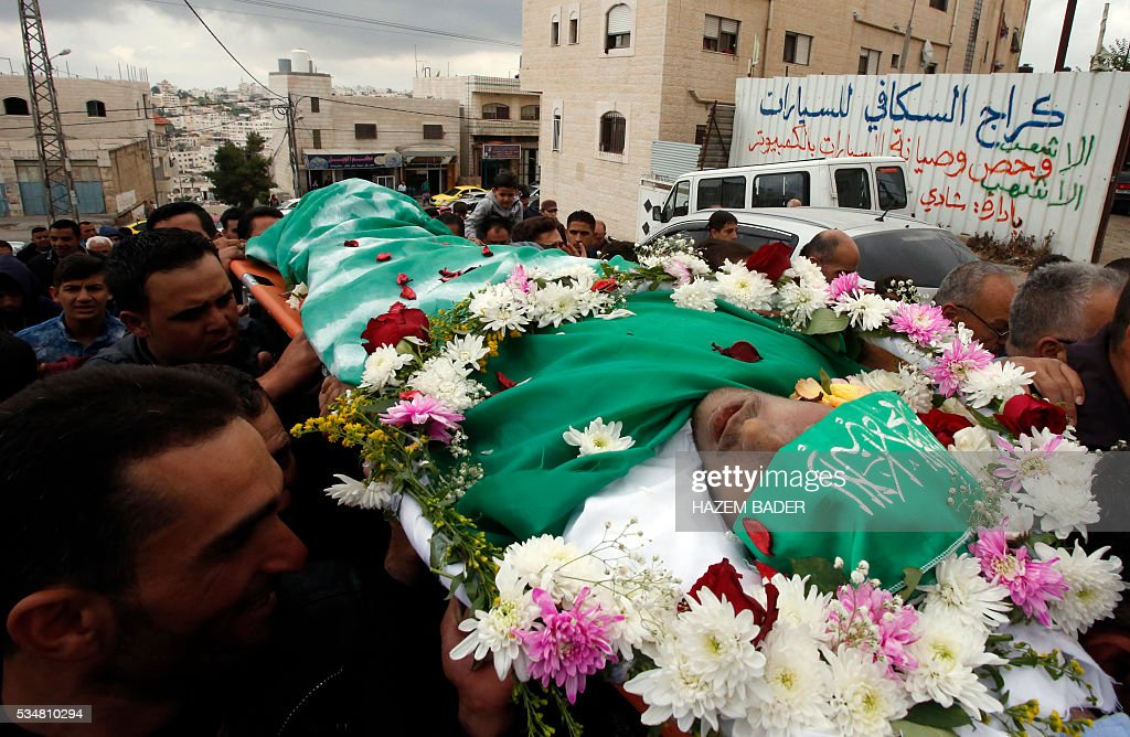 Relatives and friends chant slogans during the funeral of Abdul Fatah al-Sharif, a wounded Palestinian assailant who was shot dead by an Israeli soldier after laying prone on the ground in the city of Hebron on March 24, in the West Bank city of Hebron on May 28, 2016. An Israeli soldier caught on video shooting a wounded Palestinian assailant in the head was charged with manslaughter in a case that has sparked widespread controversy. Prosecutors presented the indictment to a military court over the March 24 killing, which occurred minutes after the Palestinian had stabbed another soldier and lay prone on the ground wounded by gunfire, according to Israeli authorities. / AFP / HAZEM