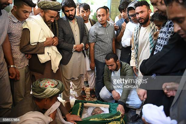 Relatives and friends gather around the coffin of Afghan reporter Zabihullah Tamanna before his funeral prayers at a mosque in Kabul on June 7 2016...