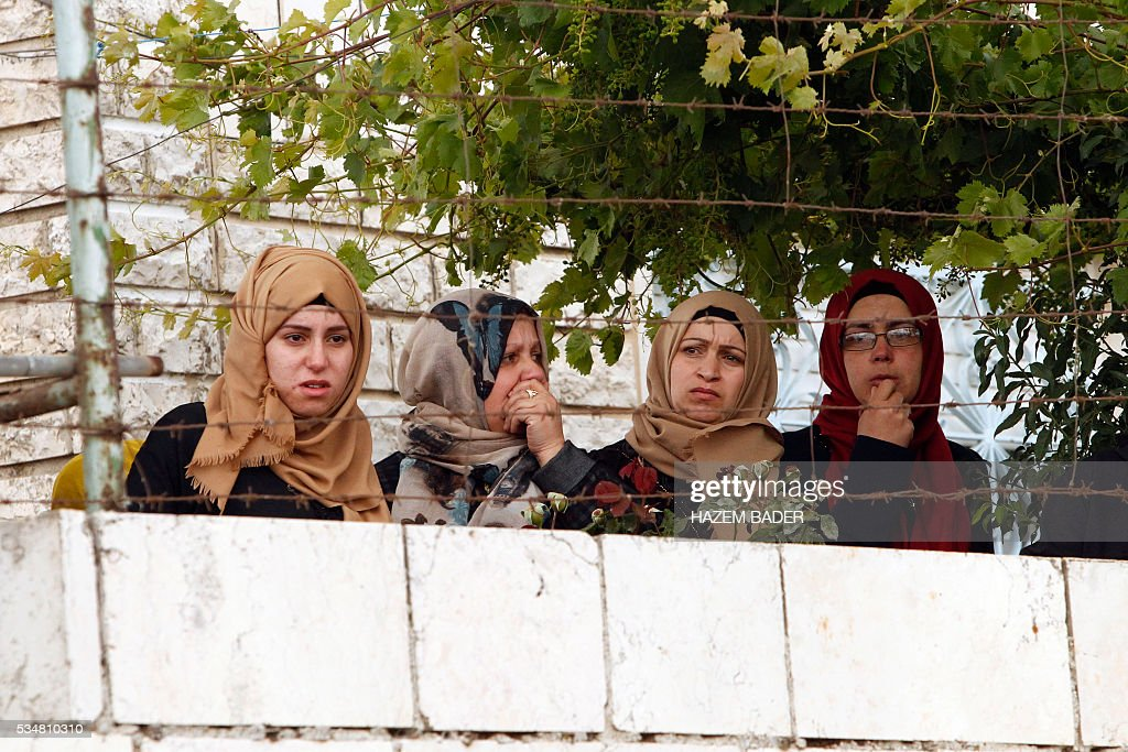 Relatives and friends mourn during the funeral of Abdul Fatah al-Sharif, a wounded Palestinian assailant who was shot dead by an Israeli soldier after laying prone on the ground in the city of Hebron on March 24, in the West Bank city of Hebron on May 28, 2016. An Israeli soldier caught on video shooting a wounded Palestinian assailant in the head was charged with manslaughter in a case that has sparked widespread controversy. Prosecutors presented the indictment to a military court over the March 24 killing, which occurred minutes after the Palestinian had stabbed another soldier and lay prone on the ground wounded by gunfire, according to Israeli authorities. / AFP / HAZEM