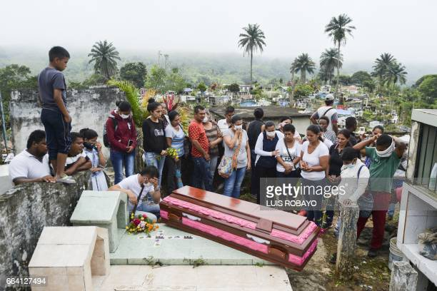 TOPSHOT Relatives and friends of Deisy Rosero pray during her funeral at a cemetery in Mocoa Putumayo department southern Colombia on April 3 2017...