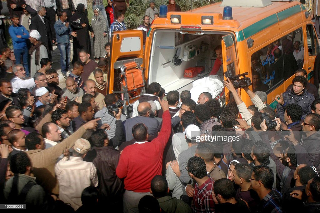 Relatives and friends of Egyptian protesters who were killed in Suez during clashes with riot police yesterday, load a body onto an ambulance outside the morgue in Suez on January 26, 2013. Twenty-two people were killed in Port Said after 21 Egyptian football fans and club members were sentenced to death over a deadly post-match riot last year in the canal city. AFP PHOTO / STR