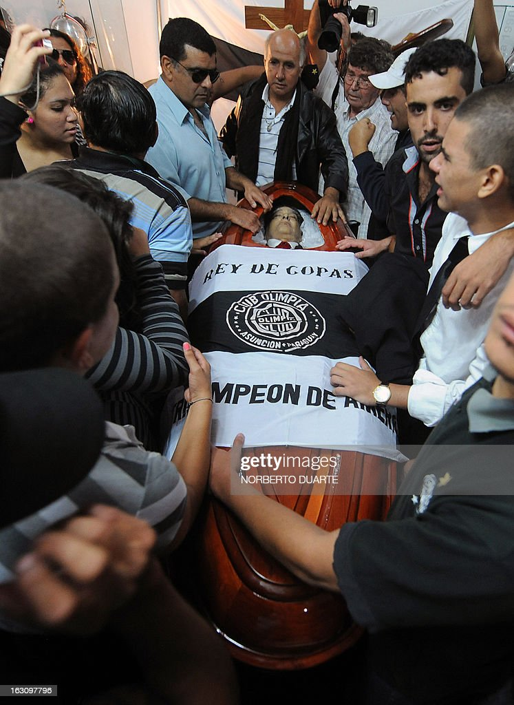 Relatives and friends of legendary Uruguayan footballer and coach Luis Cubilla mourn next to his coffin, during his wake at the Olimpia football club headquarters in Asuncion, on March 4, 2013. Cubilla died on March 3, 2013 from stomach cancer at the age of 72. In a long and colourful career, the speedy winger played for Penarol in his native country, Barcelona in Spain and River Plate in Argentina before returing home to play for Nacional. He also played for his country in three World Cups in 1962, 1970 and 1974. Cubilla then turned his hand to coaching and he led Olimpia Asuncion to 10 league titles in Paraguay before winning honours in Uruguay and Colombia as well as two Libertadores Cups and one Intercontinental Cup. AFP PHOTO / NORBERTO DUARTE