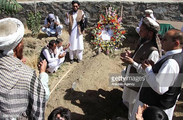 Relatives and friends of slain journalist Zabihullah Tamanna pray on his grave in Kabul Afghanistan on June 8 2016 Anadolu Agency freelancer...