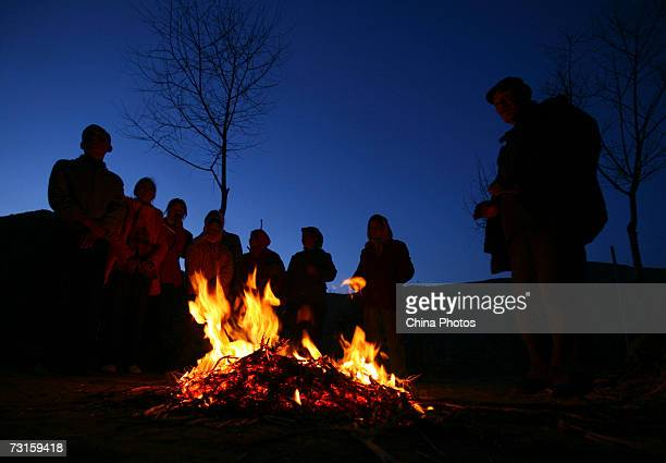 Relatives and friends of the groom get warm around a needfire outside the bride's home during a Tu ethnic minority group wedding ceremony on January...