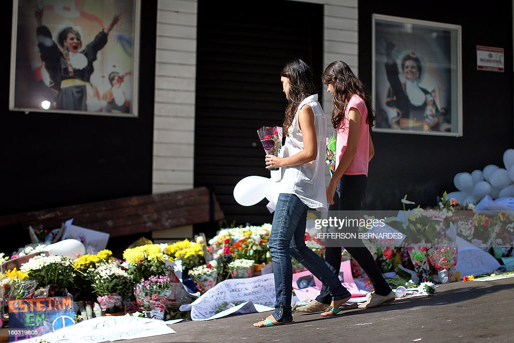 Relatives and friends of victims put flowers in front of the Kiss nightclub in Santa Maria, southern Brazil on January 29, 2013 where a blaze Sunday early morning left a death toll of over 230. Police in Brazil arrested four suspects Monday after a nightclub fire killed 231, left dozens more clinging to life, and forced officials to defend readiness for the Olympics and World Cup.