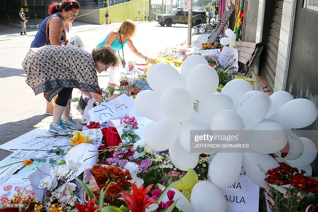Relatives and friends put flowers in front of the Kiss nightclub in Santa Maria, southern Brazil on January 29, 2013 where a blaze Sunday early morning left a death toll of over 230. Police in Brazil arrested four suspects Monday after a nightclub fire killed 231, left dozens more clinging to life, and forced officials to defend readiness for the Olympics and World Cup.