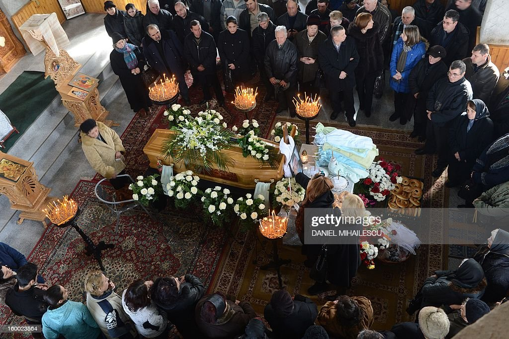 Relatives and friends stand next to the coffin of Tiberiu Ionut Costache, 36, one of the two Romanian victims who were killed during the Algerian hostage crisis, at the Orthodox church in Barcanesti village (50km north of Bucharest), January 24, 2012. Three other Romanians escaped the audacious attack by Islamist militants on a gas plant in the Algerian desert.