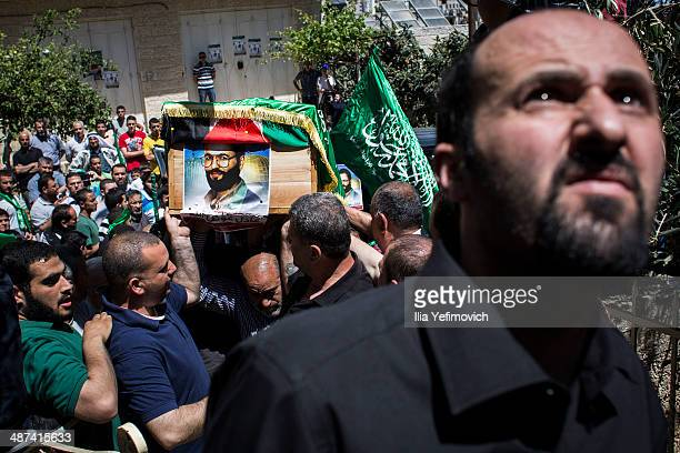 Relatives and Hamas supporters carry a coffin of one of the two Hamas members Adel and Imad Awadallah during their funeral on April 30 2014 in...