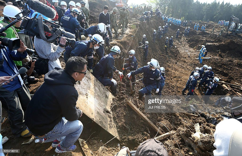 Relatives and journalists watch police officers search for missing victims in the village of MinamiAso Kumamoto prefecture on April 19 2016 Two major...