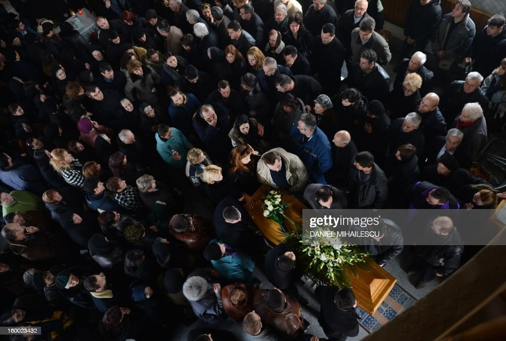 Relatives and locals attend the funeral service for Tiberiu Ionut Costache, 36, one of the two Romanian victims who were killed during the Algerian hostage crisis, at the Orthodox church in Barcanesti village (50km north of Bucharest), January 24, 2012. Three other Romanians escaped the audacious attack by Islamist militants on a gas plant in the Algerian desert. AFP PHOTO / DANIEL MIHAILESCU