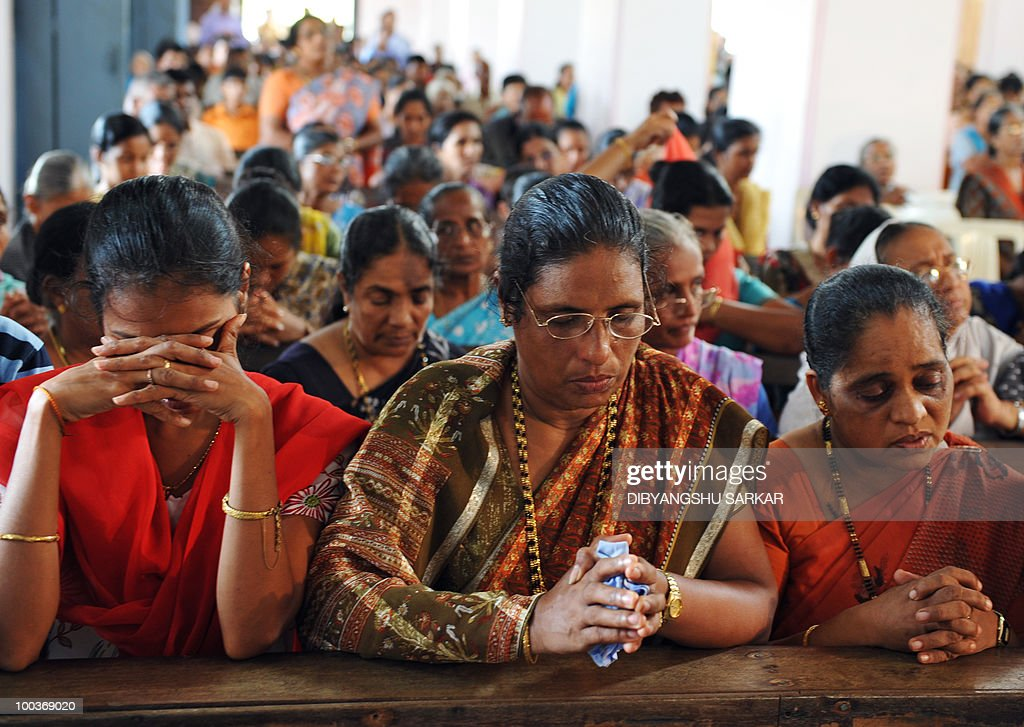 Relatives and mourners attend a funeral service for Air India Express crash victims Naveen Walton Fernandes and his wife Savitha Philomene D'Souza at the Holy Cross Church in Mangalore on May 24, 2010. Investigators on May 22 widened the search for the 'black box' data recorder of an Air India Express that crashed into a gorge killing 158 people, as the airline denied lax safety claims. AFP PHOTO/Dibyangshu SARKAR
