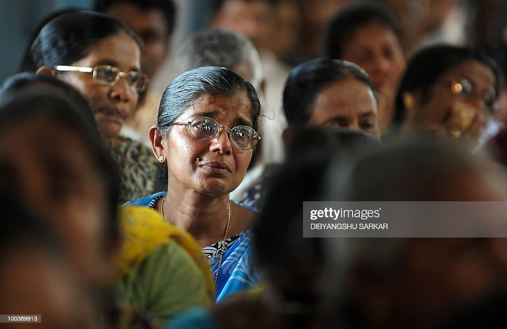 Relatives and mourners attend a funeral service for Air India Express crash victims Naveen Walton Fernandes and his wife Savitha Philomene D'Souza at the Holly Cross Church in Mangalore on May 24, 2010. Investigators on May 24 widened the search for the 'black box' data recorder of an Air India Express that crashed into a gorge killing 158 people, as the airline denied lax safety claims. Indian authorities said the cockpit voice recorder from the Boeing 737-800 was found late Sunday but the hunt was still on for the 'black box' that records all flight data and could hold the answer to the disaster. AFP PHOTO/Dibyangshu SARKAR