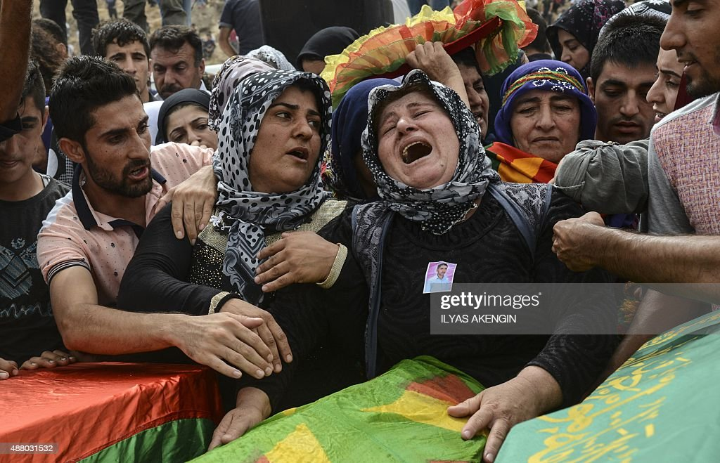 Relatives and mourners gather around the coffins of people killed during clashes between Turkish forces and militants of the Kurdistan Workers' Party...