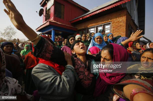 Relatives and native villagers mourn as people carry the body of Indian slain policeman Abdul Salam Khan during his funeral procession at Kareva...