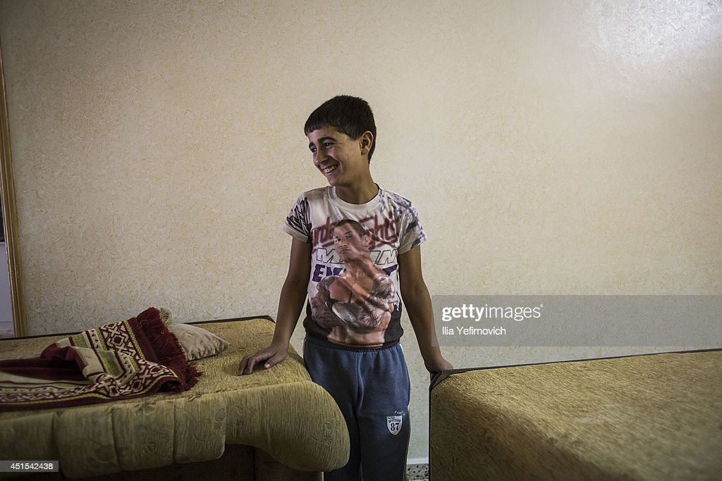 Relatives and neighbours of one of the main suspects Amer AbuAisheh are seen in a house destroyed by the Israeli army in response to the murdered...