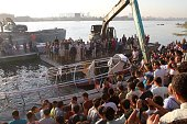 Relatives and onlookers gather on the bank of the Nile on July 23 north of the Egyptian capital Cairo as the wreckage of a boat is pulled out of the...