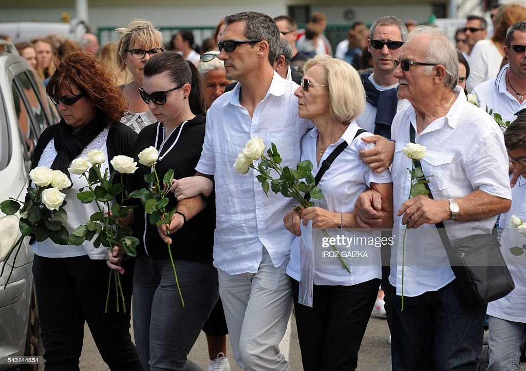 Relatives and people holding flowers take part in a march in memory of Carla, Emma and Christel Delval on June 26, 2016 in Anglet, southwestern France. Carla, Emma and her mother Christel Delvala were shot dead on June 21 by their father and husband before killing himself. / AFP / IROZ