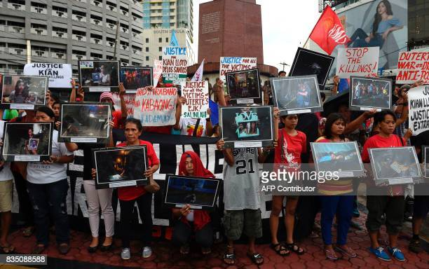 Relatives and supporters of victims of extra judicial killings hold portraits of relatives allegedly killed during antidrug raids by police during a...