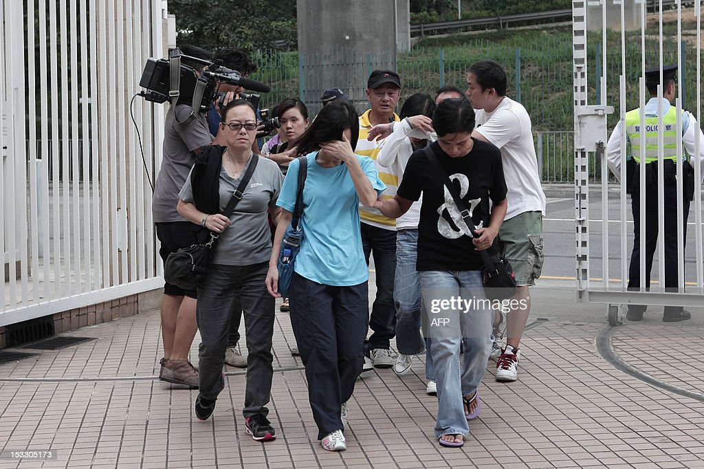 Relatives (C) are surrounded by members of the media as they arrive at the Kwai Chung public mortuary to identify victims of a boat collision in Hong Kong on October 3, 2012, two days after a ferry collided with a pleasure boat killing at least 38 people a short distance from Lamma island. More than 120 passengers and crew were on the Hong Kong Electric company's Lamma IV to watch a huge National Day fireworks display in Victoria Harbour when the accident occurred just off Lamma, an island to the southwest of Hong Kong.