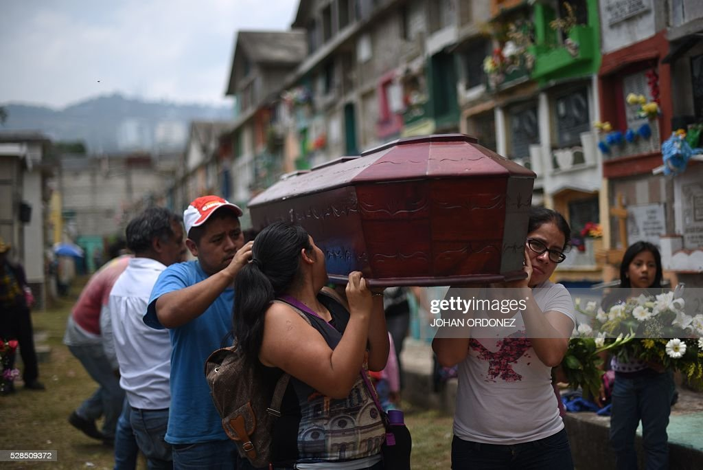 Relatives attend the burial of Lesvia Lopes, one of the victims of October 1st 2015 landslide, in Santa Catarina Pinula municipality, some 15 km east of Guatemala City, on May 5, 2016. Guatemala on Thursday buried the last bodies of victims of a tragedy caused seven months ago, when the mudslide of a hill buried El Chambray II village. / AFP / JOHAN