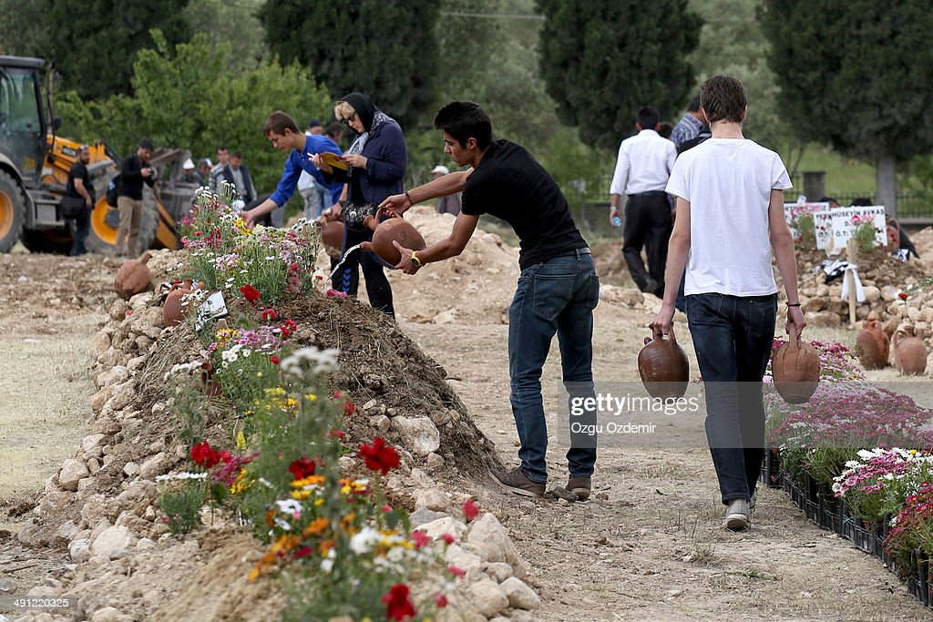 Relatives attend the graves of miners in the cemetery on May 16 2014 in Soma Turkey Rescuers are still trying to reach parts of the coal mine in Soma...