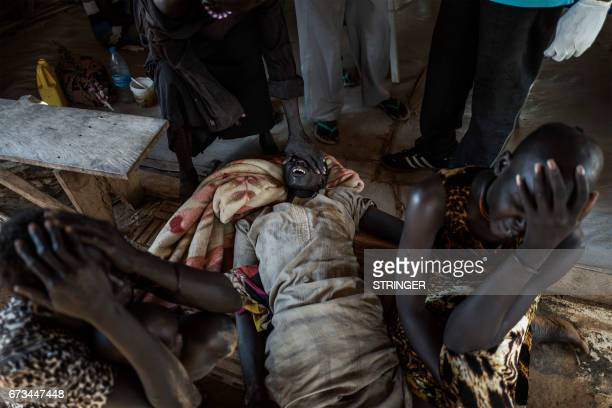 TOPSHOT Relatives begin to mourn moments after a patient with cholera dies at the temporary specialized hospital in Mingkaman a camp for the...