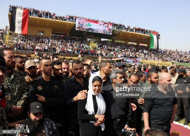 Relatives Brigadier General Issam Zahreddine are escorted through a stadium as Syrians gather to attend his funeral in the southern city of Suwaida...