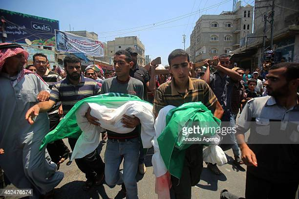 Relatives carry dead bodies of children during the funeral ceremony for the 25 Palestinians killed in Israeli shelling in Khan Yunis on July 21 2014...