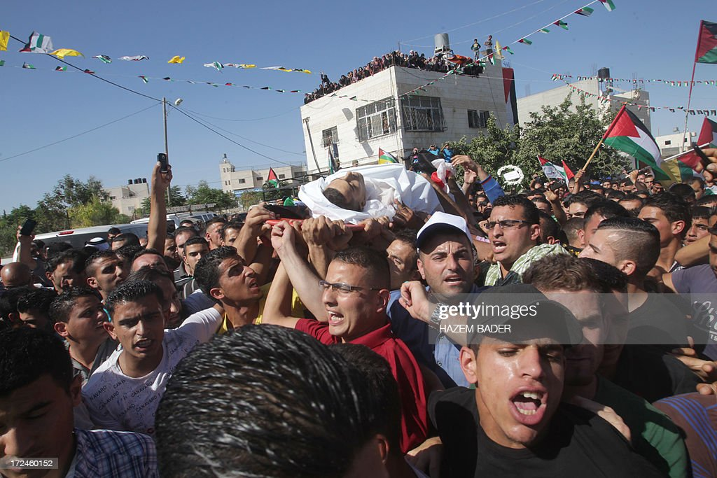Relatives carry the body of Palestinian youth Moataz Sharawna, 19, during his funeral in the West Bank village of Dura on July 2, 2013, after he was knocked down and killed by an Israeli military jeep during overnight clashes in the village. Sharawna died after being hit by the vehicle following several hours of clashes between stone throwers and troops which began at midnight in Dura, which lies just southwest of Hebron, a police spokesman told AFP.