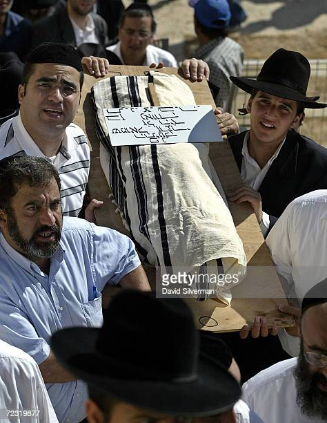 Relatives carry the small shroudcovered body of 11monthold Jewish boy Shmuel Zargari during his funeral August 20 2003 in Jerusalem's Givat Shaul...