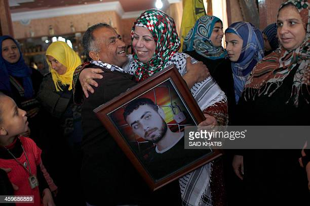 Relatives congratutale the mother of Palestinian prisoner Ramy Barbakh as she holds his picture in their home in Khan Yunis in the southern Gaza...