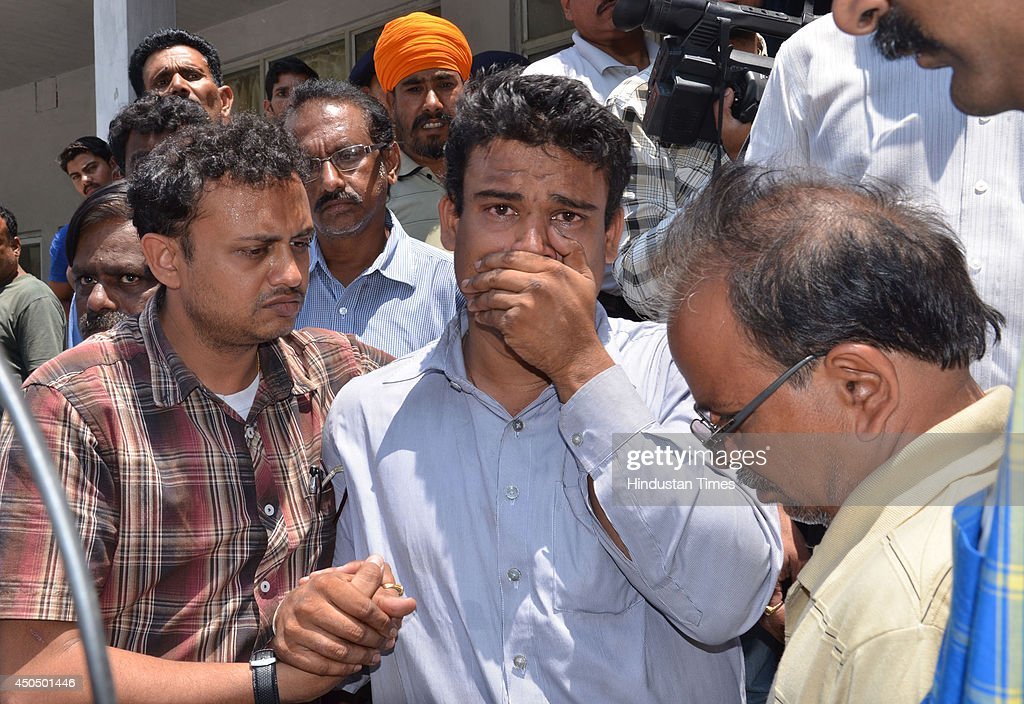 Relatives cry after they identified dead body of Gannoor Arvind Kumar which was recovered from Beas river during search operation on June 12, 2014 in Mandi, India. The rescue team had recovered six bodies so far from the river. A wall of water washed away 24 engineering students and a tour operator Sunday evening after water was released into the river allegedly without a warning from a nearby Pandoh Dam on Beas River.