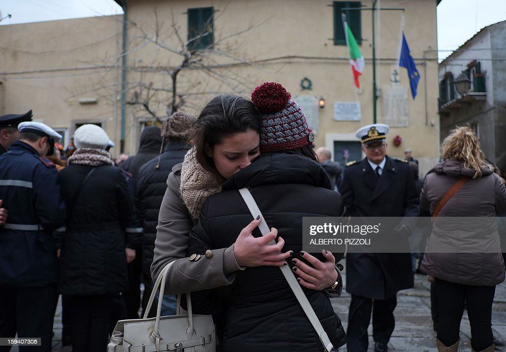 Relatives cry during the unveiling ceremony of a plaque with the names of the victims of the Costa Corncordia cruise ship in the port in the Italian island of Giglio on January 13, 2013. Survivors, grieving relatives and locals on the island of Giglio gathered on January 13 to mark the first anniversary of the Costa Concordia cruise ship disaster, which claimed 32 victims.
