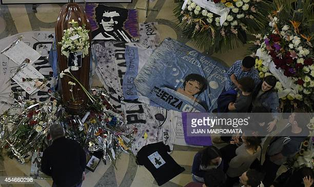 Relatives friends and fans mourn before the coffin bearing the remains of the late Argentine artist Gustavo Cerati during his funeral at the...