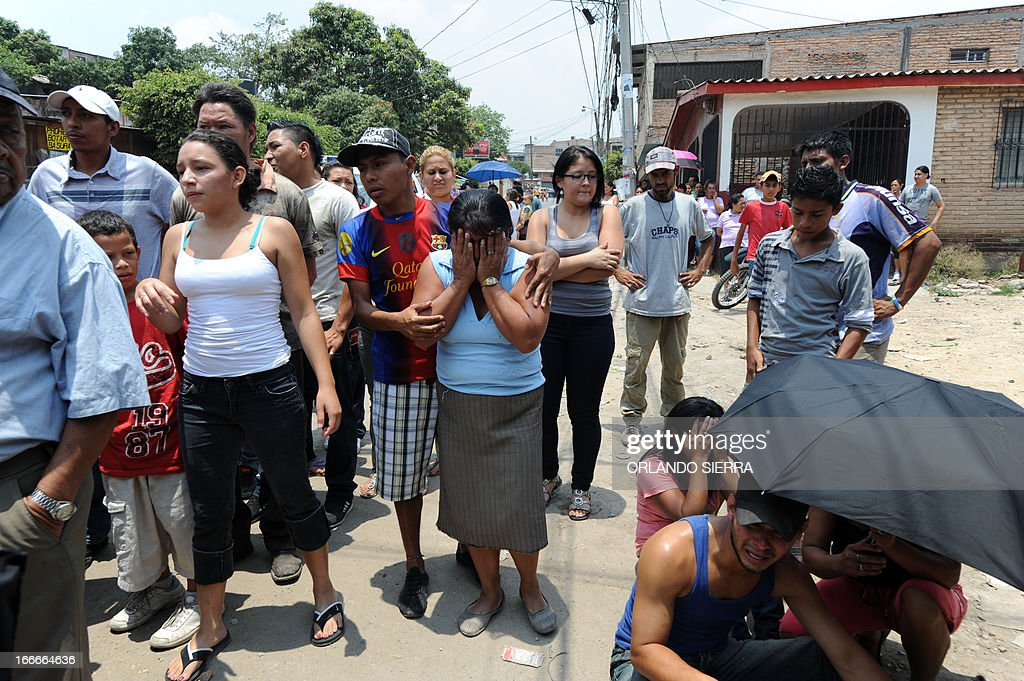 relatives, friends and passers-by gather near the crime scene in which five people -- including a high school student -- were shot dead in the suburb of La Haya, in northern Tegucigalpa, on April 15, 2013. In March 2012, the UN announced Honduras had the world's highest murder rate, at 82.1 deaths per 100,000 people, while a local observatory on violence put the rate at 86.5 per 100,000. AFP PHOTO/Orlando SIERRA