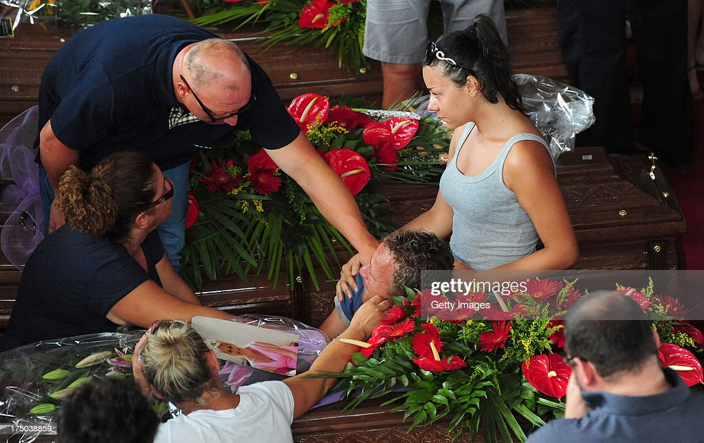 Relatives gather to grieve near to the coffins of the victims of the Monteforte Irpino coach crash during the funeral held at a local indoor sports arena on July 30, 2013 in Pozzuoli, Italy. In the second major European transport disaster in a week, 39 people were killed when a coach bus fell from a viaduct near Monteforte Irpino, Italy on July 28.